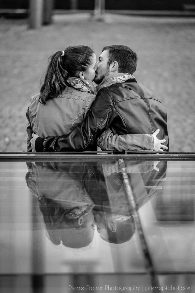 A couple kissing, with a nice reflection.