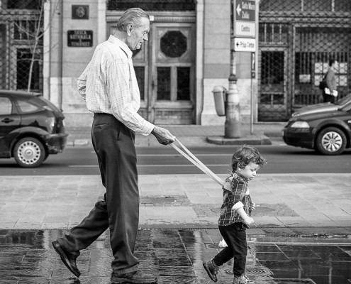 On a tight leash. A kid and his grandfather, playing between the water fountains in Cluj-Napoca, Romania.