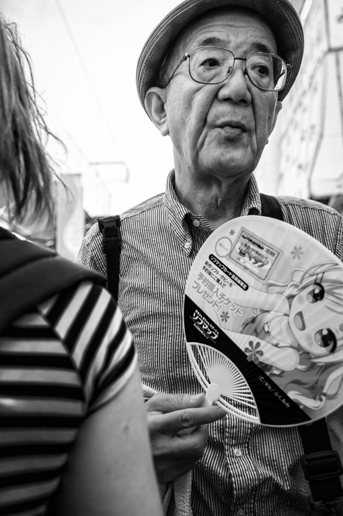An old man with a cute fan in Ameyoko shopping street, Ueno, Tokyo, Japan.