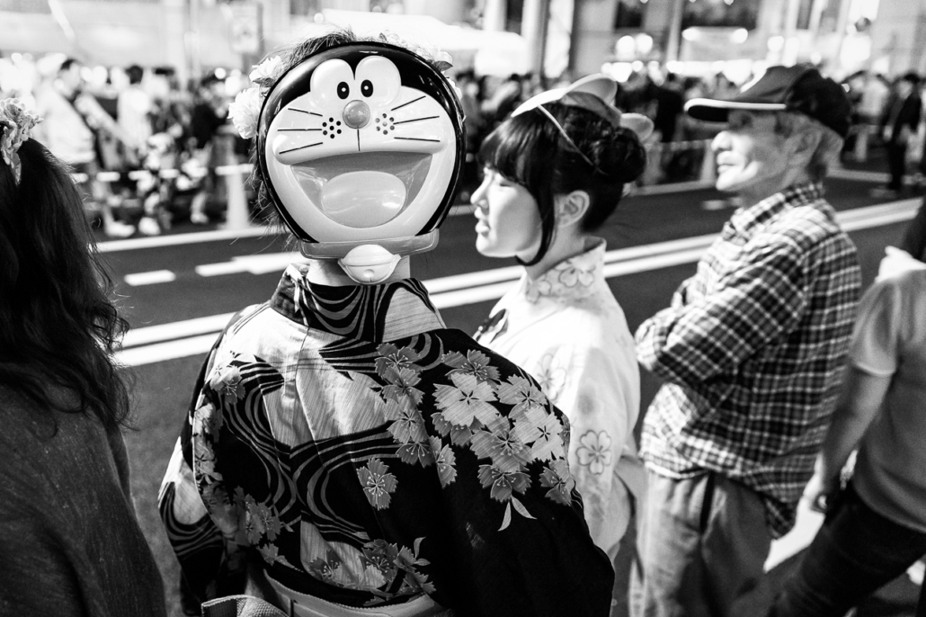 A young woman in yukata wearing a Doraemon mask in the back of her head during the Toukasan Yukata Festival in Hiroshima, Japan.